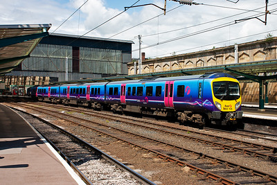 185106 departs Carlisle working 1M95 1200 Edinburgh to Manchester Airport. The electric blue livery with stripes is quite striking especially when lit by the sun.