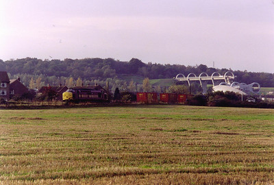 The Falkirk Wheel, linking the Union and Forth and Clyde Canals, provides the backdrop to 37416 heading for Grangemouth as 6N32 0837 MX off Mossend enterprise service.