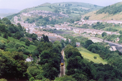 Looking north towards Brithdir and the railway runs through the centre of the scene. 37408 threads through the trees with 2F30 1315 away from Rhymney.  Much landscaping is going on the remove any last trace of the coal mining that once dominated the Welsh Valleys.  The new road to the right is built on a former colliery line.