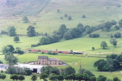 Viewed across the valley from the east side, D6990 or 37411 growls up grade to the south of Pontlottyn. This loco has been repainted into BR green and it carries its preTOPS number. The train is 2R14 0959 from Cardiff.