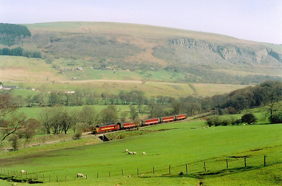To the south of Rhymney a wonderful vista is obtained from the main road. In glorious hot sunshine 37408 climbs against the grade making a wonderful sound. The train ID is 2R26 1259 from Cardiff.