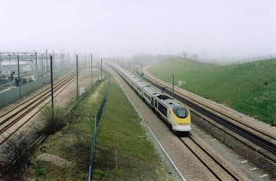 A misty Dollands Moor a few days later and 3232/31 runs beside the freight yard with 9039 1519 Paris to London working. To the right of the shot are the conventional lines.  29/3/2005