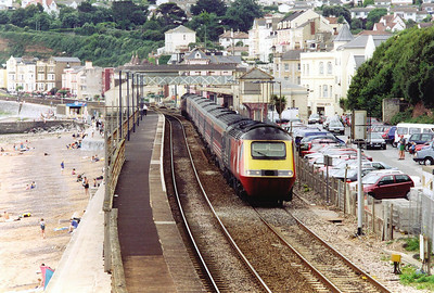 "A Virgin high speed set shakes the disused and boarded up but listed signalbox with a long distance train from Penzance to Edinburgh, 0922 off. Train ID 1S35 carries the name ""The Cornishman"" with powercars 43097 and 43078."