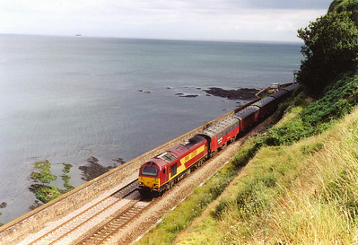 With the sun sun shining down on the railway, EWS type 5 67029 brings the lengthy 1E43 1509 Plymouth to Low Fell loaded mail vans along the sea wall section at Horse Cove.  There is no public access on the seaward side of the line but there is a foot path which makes this shot possible.