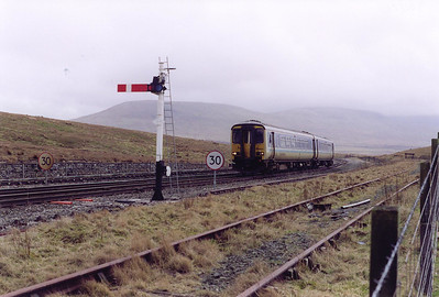 From Blea Moor to Garsdale the down line is bi-directional. 156480 is about to pass the recently installed up starter off the down line. The train is 2H92 1447 Leeds to Carlisle. The down loop is no longer in use here.