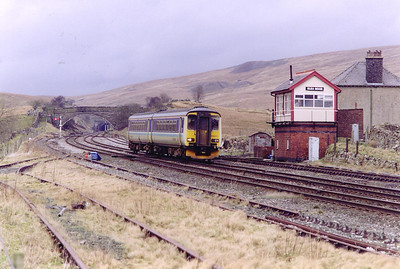 An up local passes the refurbished former Midland Railway signalbox. The ex signalman's cottage is still unoccupied despite being up for sale for several years. 156471 works 2H93 1423 Carlisle to Leeds.  Blea Moor tunnel is visible in the distance as is evidence of its construction on the hill above the unit.