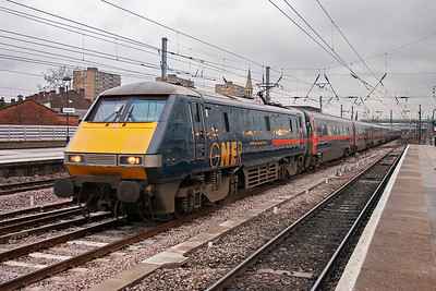 """The station lamps are reflecting on the side of 91121 which is recorded a second time as it tears through the station on the down fast line working 1S21 1500 Kings Cross to Glasgow Central, """"The Scottish Pullman""""."""