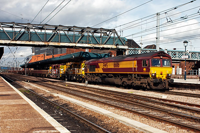 A class 7 departmental working comes south through platform 2, 66116 leads 7D08 from York and will terminate at Doncaster's Up Decoy Yard. The train is made up of 28 MTS and MHA spoil wagons and a couple of cranes.