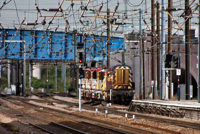 """A long lens shot to the north of the station and below the """"knitting"""" of the OLE is class 08 shunter 08514 bringing a short engineers train made up of several cranes south."""