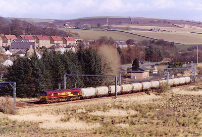 A change from the usual diet of loaded and empty coal trains is this working, 6S54 1130 North Blyth to Fort William loaded alumina tanks. 66100 is routed into the down loop to be passed by a northbound passenger train.