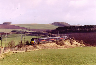 "This location is near Reston and is about 8 miles from the England - Scotland border. The down ""Highland Chieftain"" comes north with 43120 and 43119 on either end of the HST set. The train details are 1S24 1200 Kings Cross to Inverness."