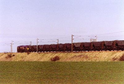 An empty set of HAA coal hoppers rattle along the ECML to the south of Dunbar with 66141 at the head. It is 6S35 0900 Tyne Yard to Millerhill.