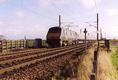 Beside the East Coast Main Line near West Barns between Edinburgh and Dunbar, 91025 speeds south propelling its train of mkIV coaches and DVT. This working is 1E06 0930 Edinburgh to Kings Cross.