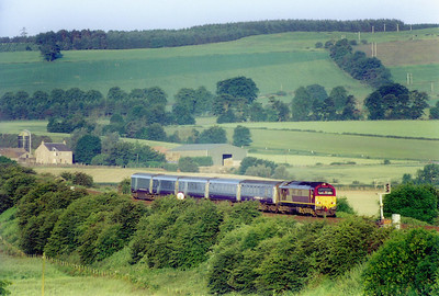 The next day dawned bright and cloudless and again I went to Welltree. 67026 runs down the 1 in 95 of Falkland Road Bank with its six coach load. The three portions split at Edinburgh, 1S25 for Aberdeen leaves at 0440.   25/6/2003