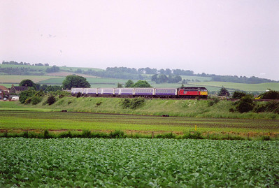 "47791 in RES livery brings its six coach train past the village of Kingskettle. The train is made up of four mkIII sleepers and two mkII seating coaches. The sleeper service is branded the ""Night Caledonian"".  27/6/2000"