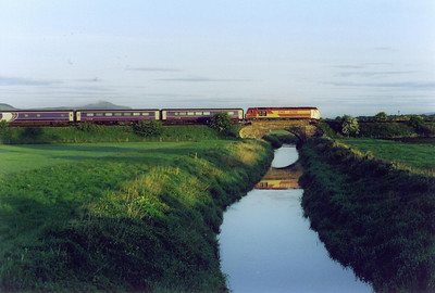 Two days after the previous shot and 67018 is still rostered to the Aberdeen portion. Right on time is comes by and crosses the River Eden with the early morning sun just glinting off the cab side and the loco reflected in the still waters of the river.  26/5/2003