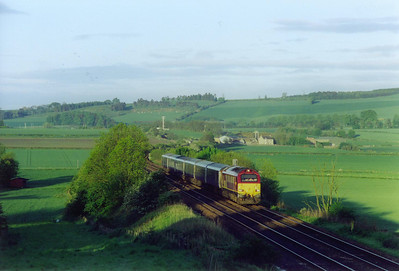 The time is 5.30am and the sun light is bright but the shadows are long. 67018 comes down the 1 in 95 gradient at Welltree with the Aberdeen portion of the joint Fort William, Inverness and Aberdeen sleeper.  24/5/2003