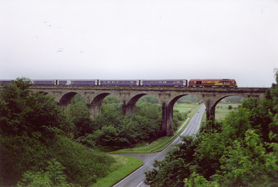 I had my camera with me at work after a promise of an early finish, my intension was to catch the sleeper. In the event I finished at the booked 6am and the sleeper was running late. 67013 passes over Markinch Viaduct running about an hour down.  4/7/2002