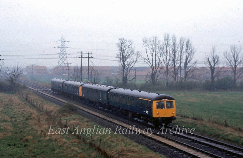 On a very dull wet morning a four car cravens set approaches the A14 bridge running empty stock to Swavesey for a special to Liverpool Street.  11th April 1981.