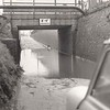 Milton Road Crossing, Cambridge. The crossing was provided with an underpass for the passage of traffic when the gates were closed. This was on the Chesterton Junction side of the gates.  After heavy rainfall the road regularly used to flood. This was the scene sometime in 1964, viewed towards Cambridge,<br /> <br /> Image:- Mike Petty