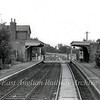 Oakington viewed from the brake van of a sand train. The guard can be seen closing the gates behind the train. Image dated 24th June 1975. To the right,  one of the station fluorescent lamps remains, five years after closure of the passenger service.