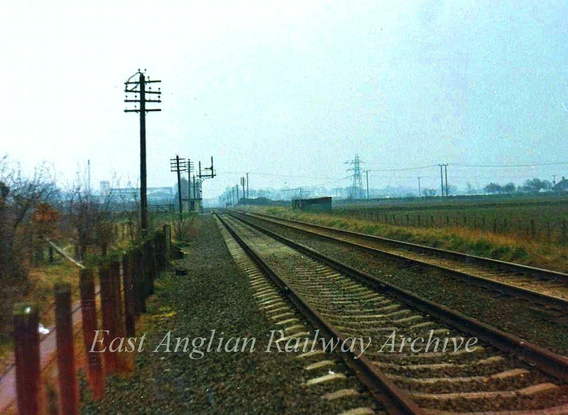 The line between Girton Road crossing and Histon looking south east towards Histon. The signal in the distance is Histon's Up Inner Distant and marks the location where the Up goods loop splits off.  March 1974