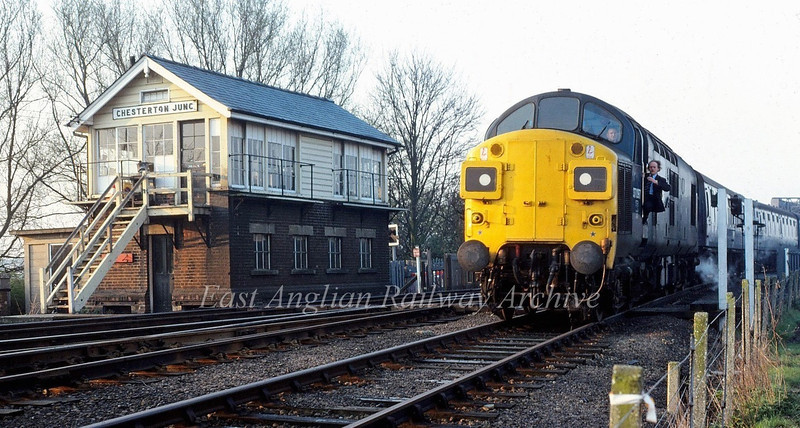 """Early morning at Chesterton Junction. 37097 heads down the St Ives branch with empty coaching stock for a Railway Development Society special to Liverpool Street on 12th April 1980. The second man is picking up the """"one engine in steam"""" token."""