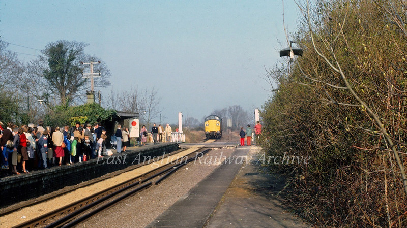 Swavesey on 12th April 1980 with a platform packed with passengers waiting for a Railway Development Society special to Liverpool Street. 37097 is approaching.
