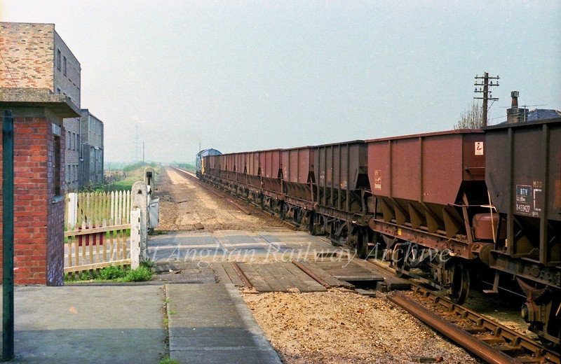 37026 heads a rake of empty sand wagons over the crossing gates at Long Stanton on 24th April 1978.