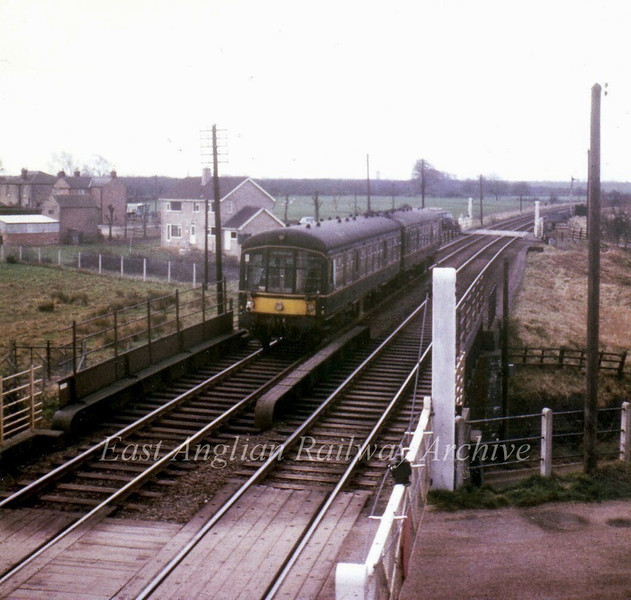 A two car Derby lightweight dmu set  E79025/E79614 leave Somersham on a March to Cambridge working on the last day of operation: 4th March 1967. In the foreground are the crossing gates and underbridge (No 2301) for Chatteris Road and in the background Colne Road crossing. View looking south from the station footbridge. Photo with kind permission of Stewart Ingram.