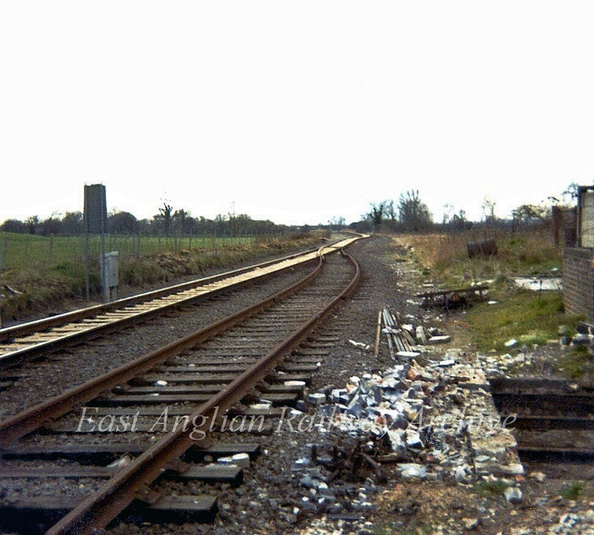 Swavesey looking west from the crossing gates. When the line to March closed in 1967 the section from here to St Ives was singled from this point with electric token working in force. The remains of the signal box can be seen to the right.  April 1973