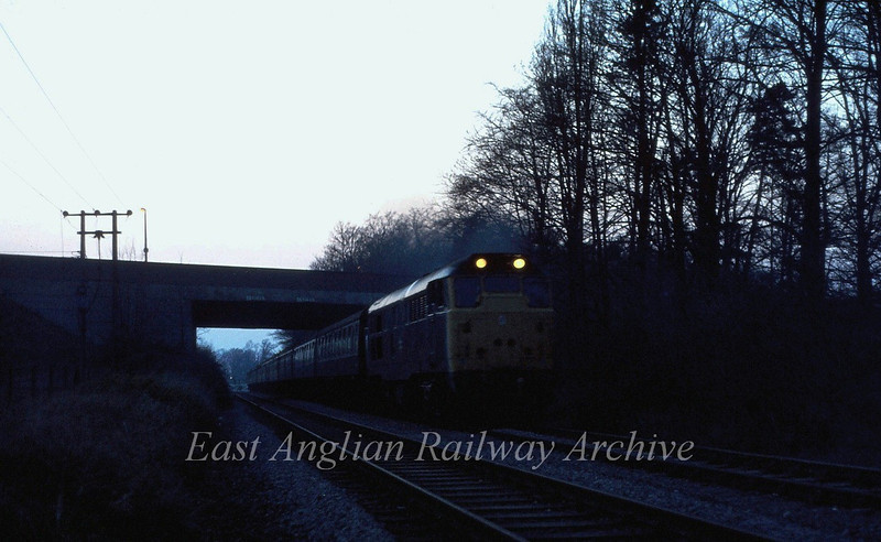 With just about enough light for a shot 31313 stands under Histon Bypass bridge with the return empty stock from the RDS special Swavesey to Liverpool Street  12th April 1980.