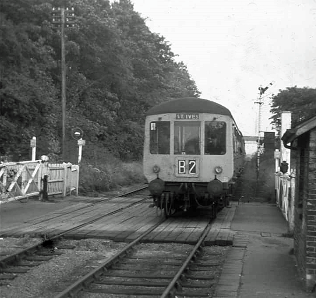 The photographer is standing on Histon's down platform as a St Ives bound dmu arrives. The year is around 1969, not long before closure of the service. Note the down home signal and the dome lamp at the pedestrian gates.<br /> <br /> Image with kind permission of Dave Gent.