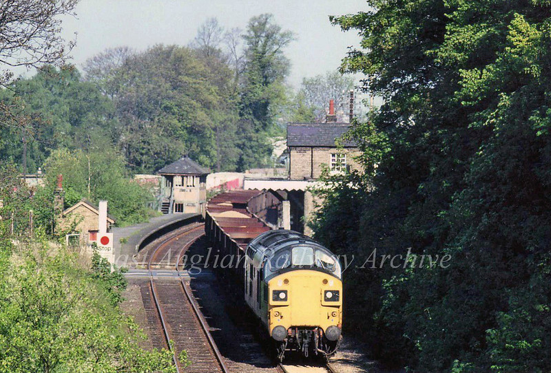 Another shot taken from the bypass bridge, but this time with a 200mm lens. An unknown class 37 heads a rake of sand wagons through Histon during the summer of 1980.