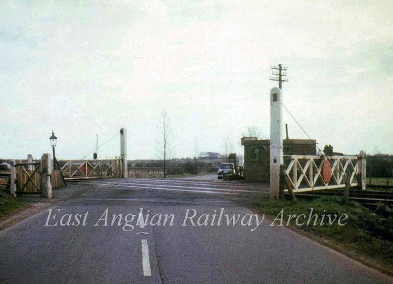 Needingworth Road crossing gates north of St Ives where the A1123 road crossed, looking towards Needingworth.  No trace remains, the area transformed by road improvements. Photo dated  4th March 1967. Note the ground frame in front of Stewart's A35.  Photo with kind permission of Stewart Ingram