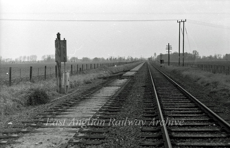 View from Girton Road Crossing Histon looking north west towards Oakington after the Down line had been lifted at this point. Approximately near the twin power line posts was the red  semaphore stop signal for the gates and below it Histon station's, motor driven, outer distant. 18th January 1976.