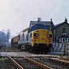 "37026 departs Histon with sand from Fen Drayton on 24th April 1978. A piece of local history here. Between the right hand eave of the station house and the grey building on top of Chivers factory to the right is a barely perceptible small black protrusion. This was a steam powered whistle with a tone of around 800 Hz which apparently served as an ""all clear"" signal for enemy action during the second world war. Chivers used it after the war to announce the start and end of shifts. It went off at 0800, 1300,1345 and 1700 and could be heard all over the village. It was always interesting to watch the spurt of steam issuing from the building at these times. It was locally known as the buzzer. All long gone now of course."