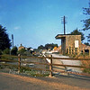 Chatteris Station facing north  on 26th August 1973. The concrete post of the Up starter signal remains on the right. Note also the staggered platfoms and the WH Smith bookstall. The station at the time was used as a highways depot. Today nothing remains ,The A141 road uses the trackbed. The demolished station building was behind the bookstall. All that remains is a mound of rubble.