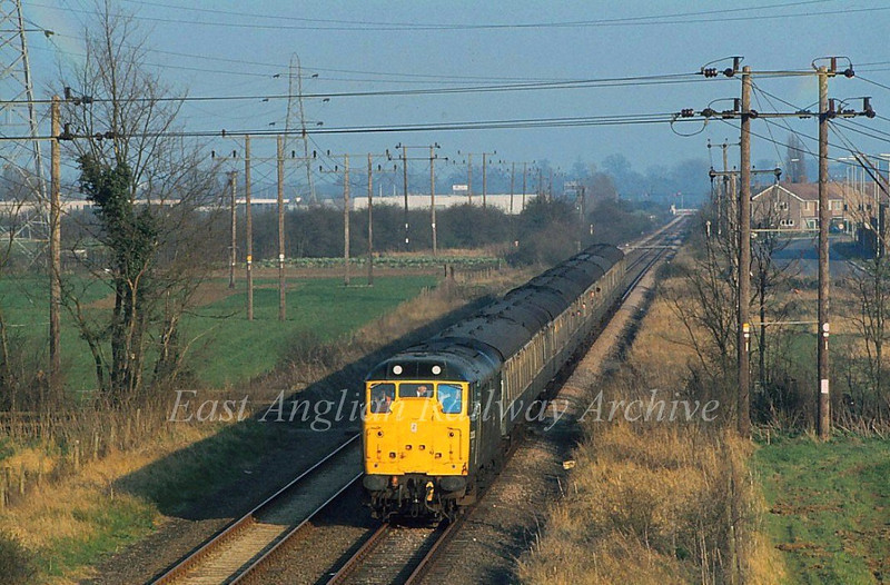 Taken from the top of the A14 Bridge with a 200mm lens. 31313 approaches with a return RDS special from Liverpoool Street to Swavesey on 12th April 1980. Kings Hedges Crossing is behind the rear carriage with Milton Road Crossing in the distance.