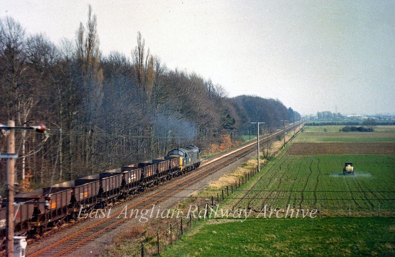 From the vantage point of Histon bypass bridge,  37131 heads towards Cambridge on a mineral working from Fen Drayton.  31st March 1974.