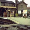 The station house and Up platform in 1961. To the right is Chiver's factory and on the platform behind the flower border, boards probably advertising holidays by rail or special excursions to Clacton/Hunstanton.  Next to the ticket office baskets of racing pigeons? await the next passenger train.   Image thanks to Pete Driver.