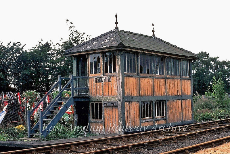 Histon Signal Box.  1st September 1980. This was located at the end of the Down Platform. It was of McKenzie and Holland design as characterised by the finials on the roof and the vertical window panes. The box originally contained 24 levers , but a new 30 lever frame was added in 1903. In the early thirties a 90 wagon Up goods loop was provided at Histon which needed 4 more levers. This required the box to be extended which can be seen to the extreme right. The box closed completely on 24th April 1972 and demolished in September 1980 after it was set alight by vandals.