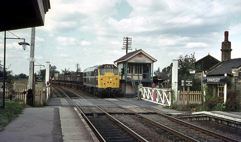 A lovely shot of Swavesey on the last day of passenger operations, 3rd October 1970. The driver of a class 31 is handing over the single line token for the Swavesey-St Ives single line section. Nothing remains today of this  scene.  Photo with kind permission of Ian Baker.