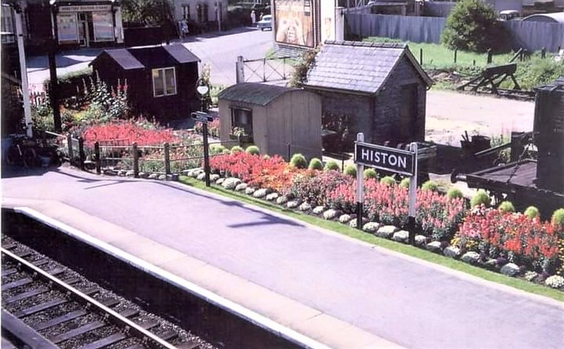 "Histon regularly won the ""Best Kept Station Award""  Here is an example of the excellent flower beds maintained by staff.  Of interest are the buildings and the presence of two sidings south of the Down platform.  In the background is Webster's Station stores on Cambridge Road and on the platform, the shadow of the Up starter signal. The metal building behind the totem is the lamp room.  Image dated 1961.  Thanks to Pete Driver."