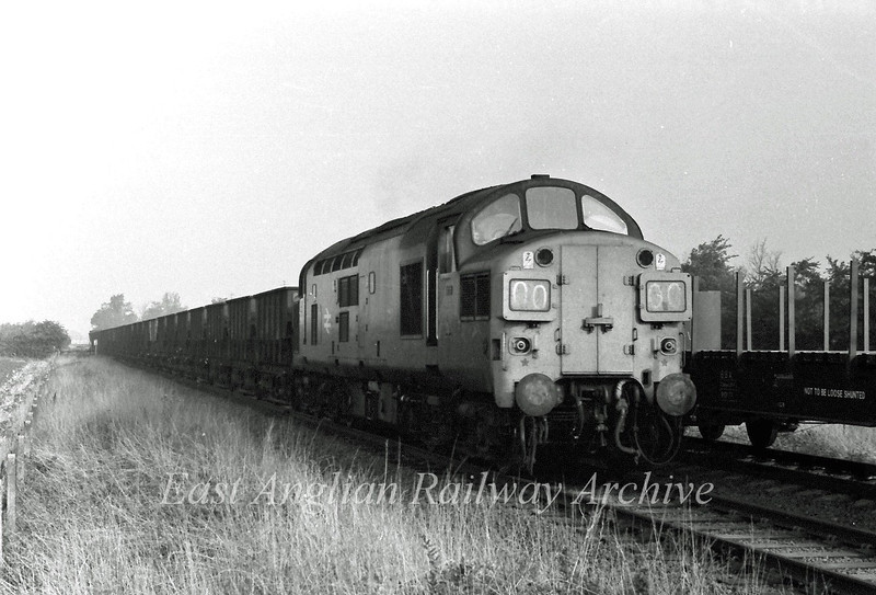 37096 passes the occupation crossing/footpath to Girton at St Audreys Close, Histon. Girton Road crossing is to the rear. The up line is out of use and at the time was used to store wagons. 8th August 1976.