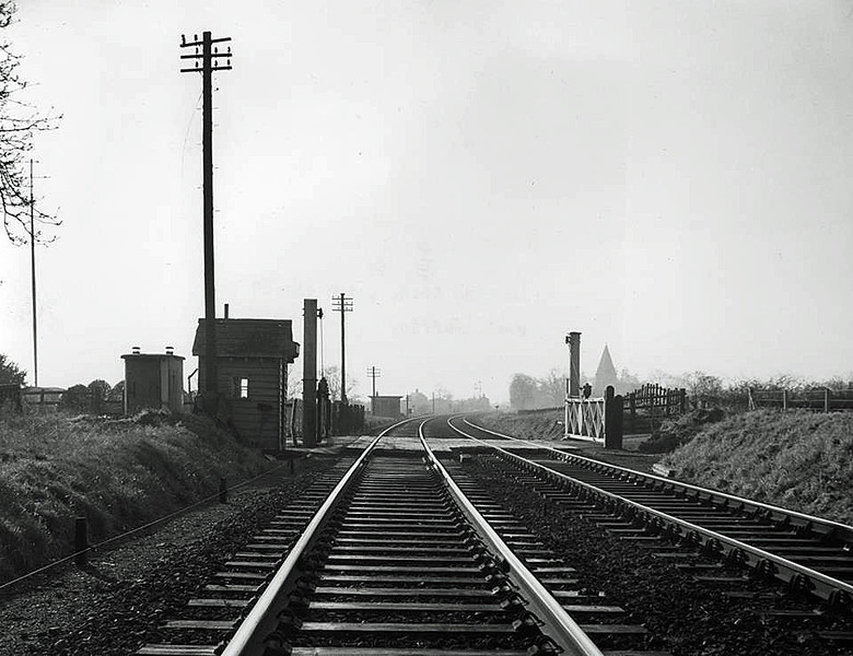 "Wimblington. Eastward End Crossing facing south towards the station on 10th January 1962. The A141 ""Isle of Ely Way"" now follows the line's alignment and no trace exists. Wimblington Church adjacent to the station can be seen to the right of the right hand gate post.<br /> <br /> Image thanks to Mark Brammer."