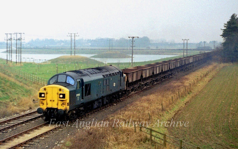 37052 passes the lakes at what is now Holiday Inn Histon, and is about to pass under the A14 Bridge on a rather murky 18th February 1980.The lakes are a result of excavations during the building of the A14