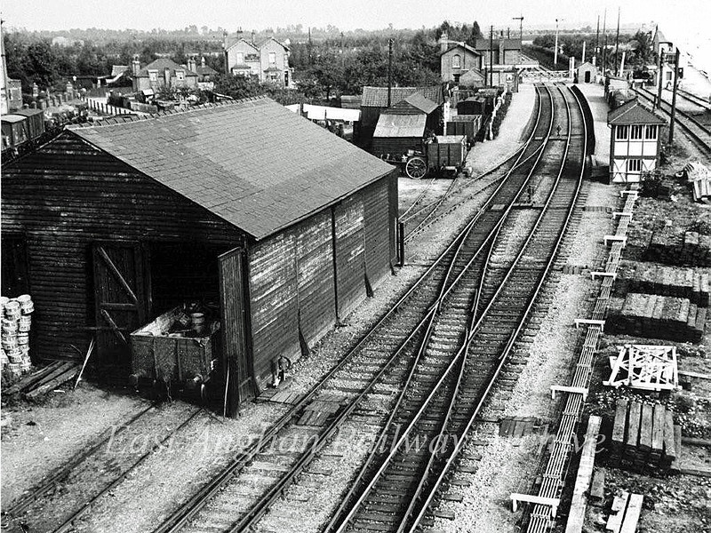 A fine view of Histon looking towards Cambridge c1903 with a clear shot of the goods shed on the left and the sidings in use at the time. To the far left can be seen the sidings allocated to the nearby Chivers Jam Factory. The photo is probably taken from the top of the up starter signal which was later moved further towards Oakington to avoid trains obstructing the crossing. Photo thanks to Mrs Eleanor Whitehead.