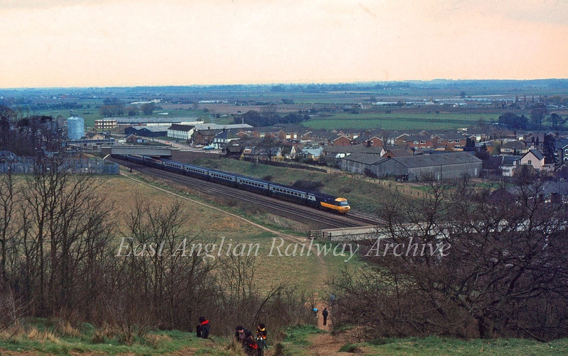 Sandy Hills give a supurb view of operations on the ECML. Here the 1400 Kings Cross to Edinburgh is passing Sandy station which can be seen behind the rear power car. 7th April 1980.