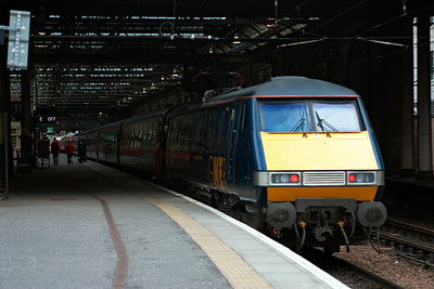 91119 is the propelling motive power for a  GNER service from Glasgow Central to London Kings Cross, 1E19 1500 off.  The doors are closed and the platform staff have indicated the train is ready to leave.